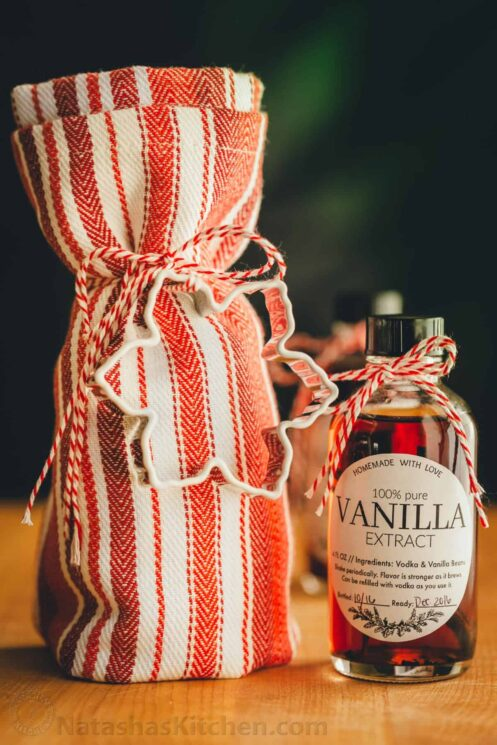 red and white striped dish towel tied with a cookie cutter and a bottle of vanilla extract