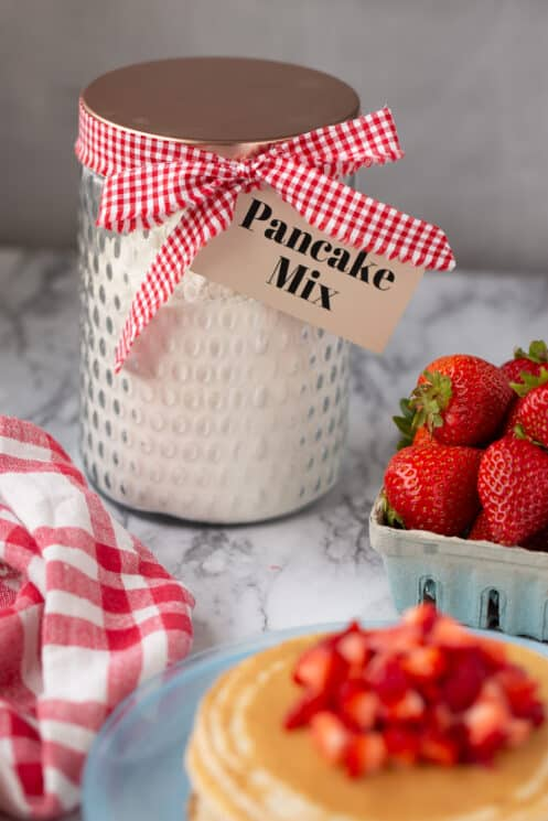 glass jar with a ribbon and a tag and a container of strawberries