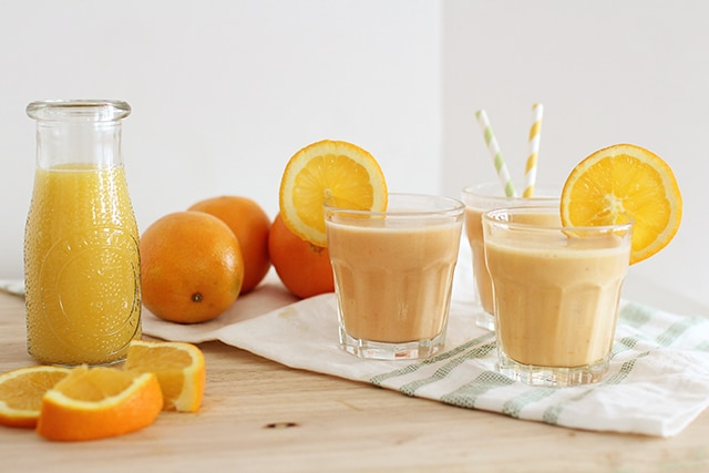 homemade orange julius in glass with fresh oranges