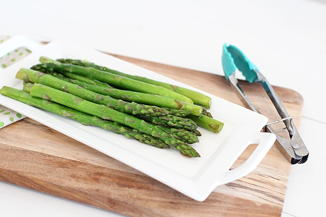 serving dish of asparagus with tongs