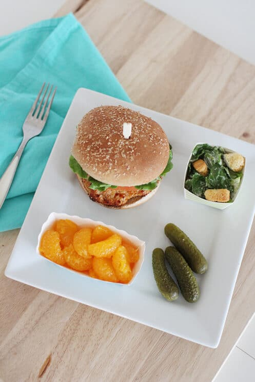 Delicious teriyaki turkey burger with pickles oranges and salad