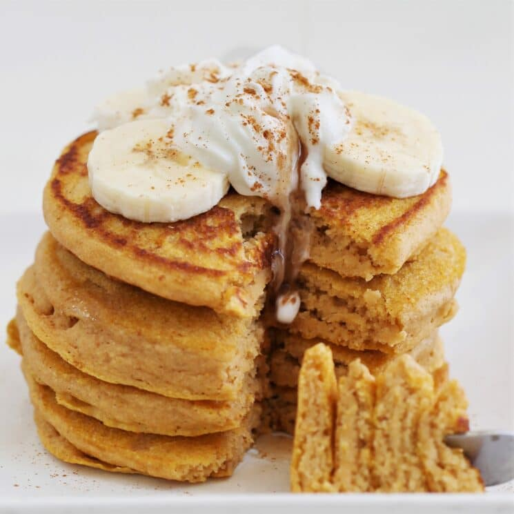 stack of sweet potato pancakes with bananas and whip cream with cinnamon on top