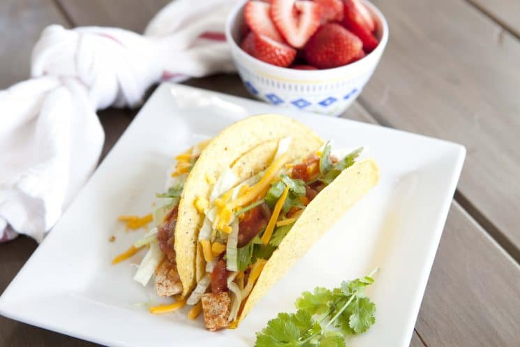 crispy chicken tacos on a square plate with strawberries