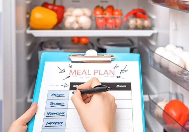 meal plan calendar on a meal plan and a person filling it out in front of an open fridge