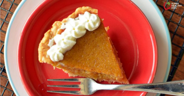 butternut squash pie topped with whipped cream on a red plate