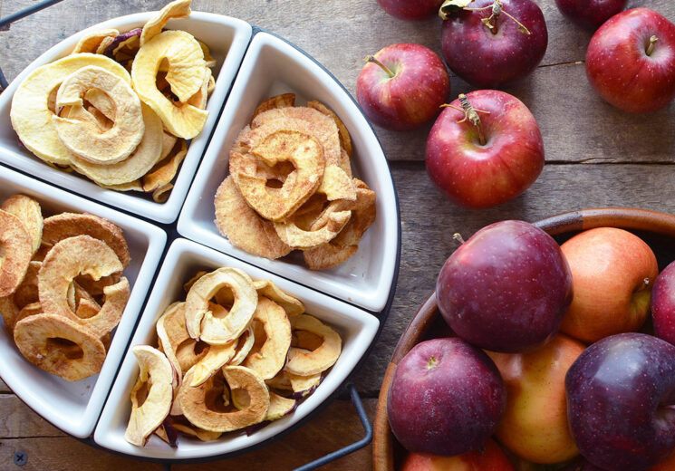Cinnamon Sugar Dried apples in a white dish with red apples in the background
