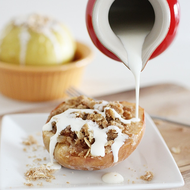 pouring cream over a baked apple