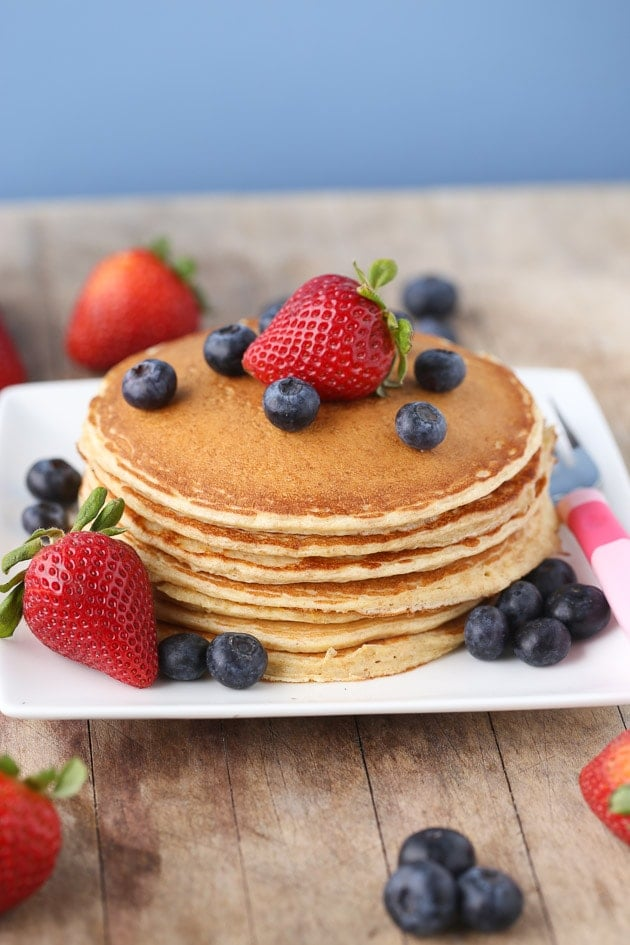 Cottage Cheese Protein Pancakes stacked on a plate with strawberries and blueberries