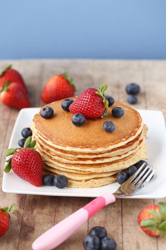 cottage cheese protein pancakes stacked on a plate with strawberries and blueberries and a pink fork