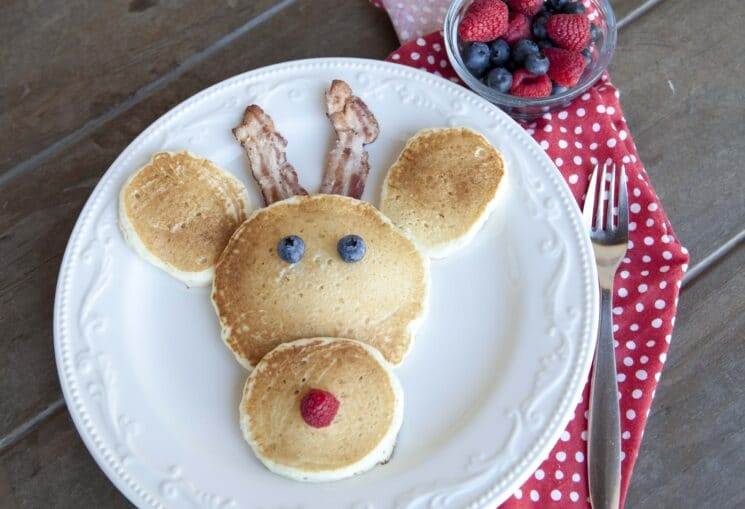 pancakes shaped and assembled to resemble a reindeer head with berries for the eyes and nose and bacon antlers