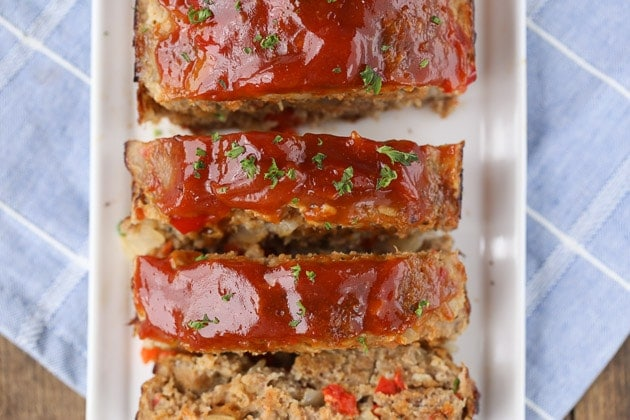 close up of turkey meatloaf showing shiny sauce and fresh herbs