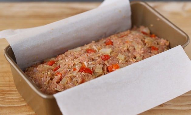 Uncooked turkey meatloaf in a pan lined with parchment paper, ready to go into the oven