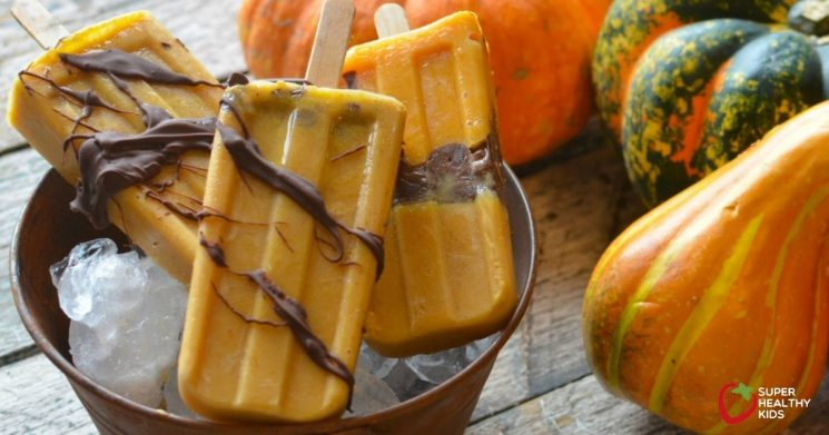 orange and chocolate popsicles in a bowl of ice with squash in the background