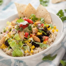 salad in a bowl with bbq chicken, corn, black beans, rice and tortilla chips
