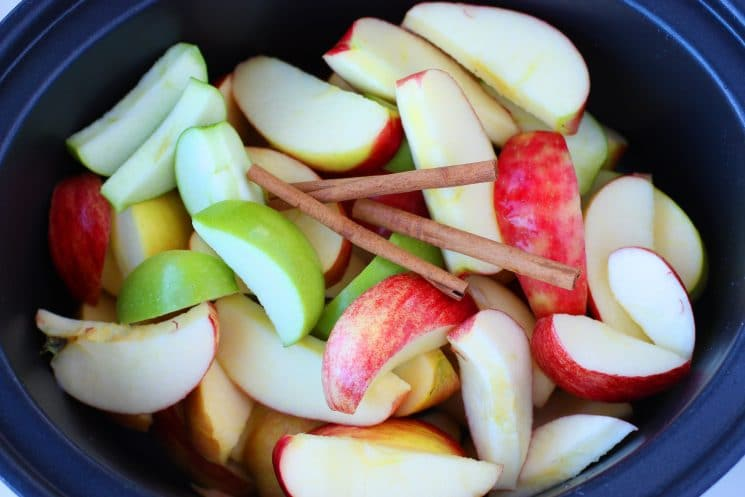 sliced apples with cinnamon sticks in the slow cooker