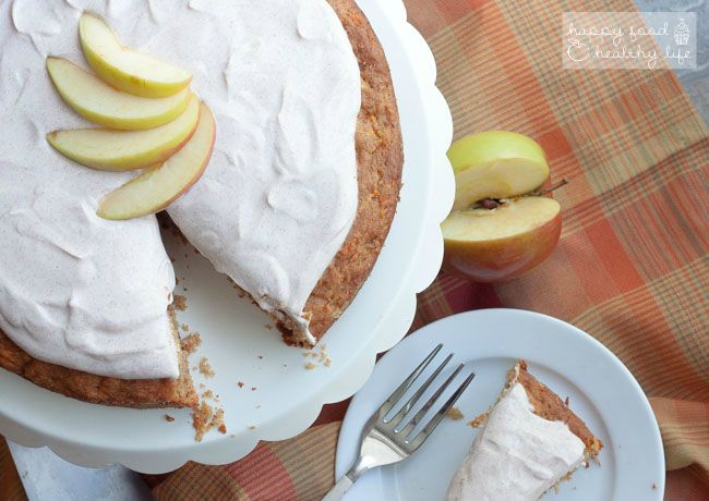 apple cake topped with white frosting  and sliced apples on a checkered tablecloth