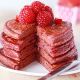 Stack of dye free pink pancakes on a plate with a slice taken out