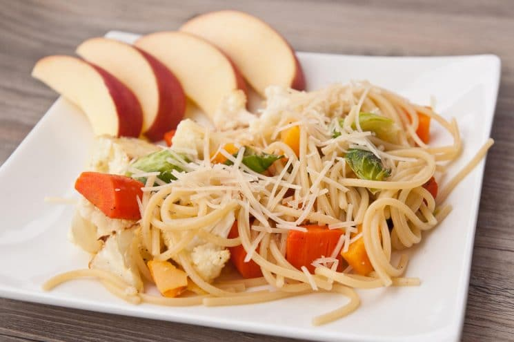 Spaghetti with vegetables and cheese on a white plate