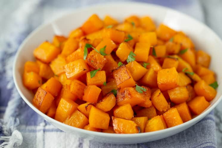 white bowl of beautifully caramelized butternut squash cubes with a sprinkle of parsley