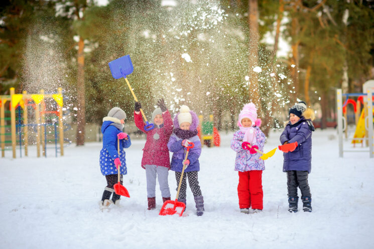 a group of kids playing in the park in the snow