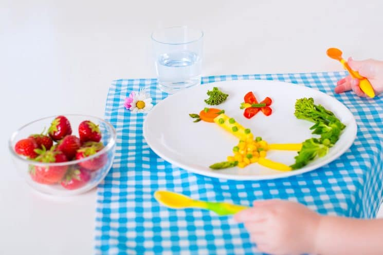 Top 20 Finger Foods For Baby - Healthy vegetarian lunch for little kids. Kid meal. Vegetable and fruit served as animals, corn, broccoli, carrot, strawberry helping child to learn eating right and clean, children hands with spoon