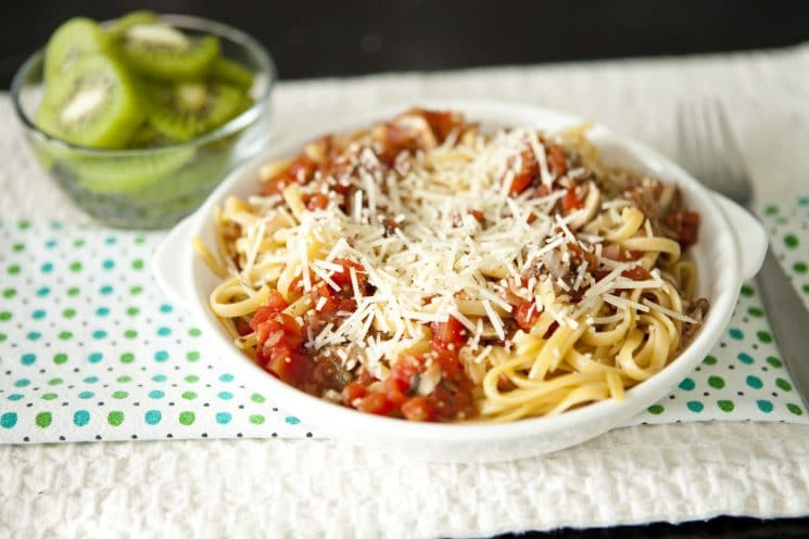 Pasta with sauce and cheese with a decorative napkin, served with kiwi