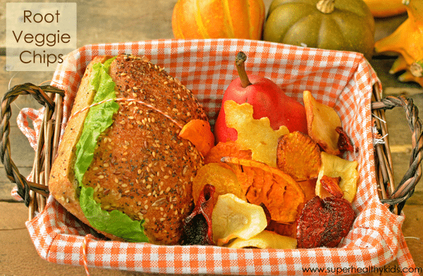 a basket surrounded by squash filled with root veggie chips and a sandwich