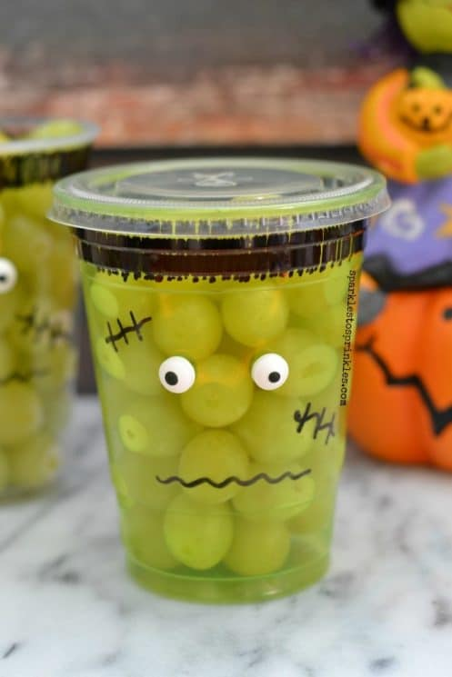 plastic cup full of green grapes and decorated to look like frankenstein