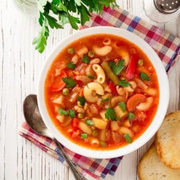 crockpot minestrone soup in a white bowl with crusty bread on the side