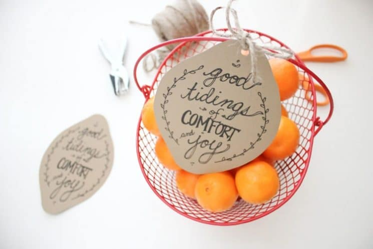 oranges in a red bowl with holiday tag