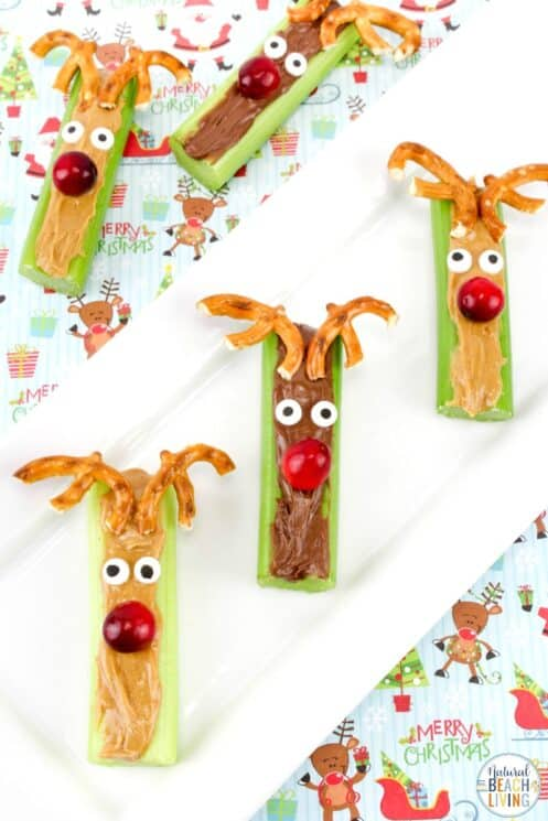 Celery stick with peanut butter or Nutella with a lingonberry as a nose and pretzels as an antler on a holiday plate