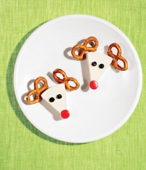 white triangle cheese with pretzel antlers on a white plate with a green background