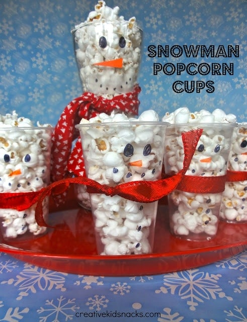 clear cups with a snowman face drawn on it filled with popcorn and tied with a ribbon