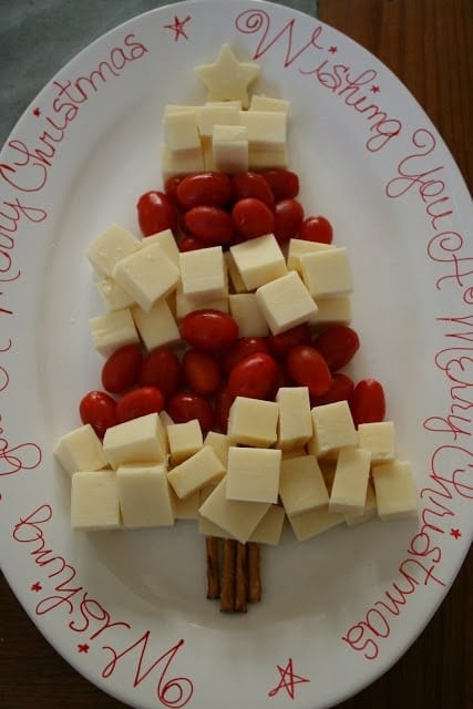 cheese cubes and cherry tomatoes shaped into a christmas tree