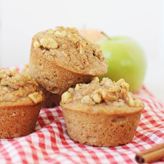 whole wheat applesauce muffins with walnuts on top on a red checkered napkin