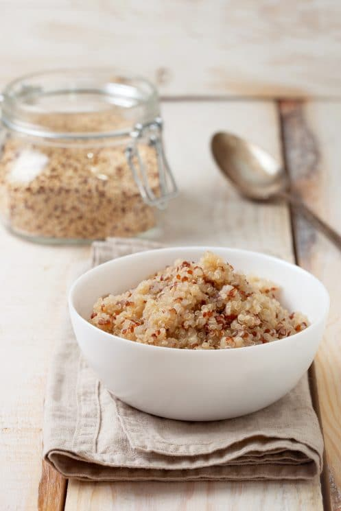 white bowl of cooked quinoa on a kitchen towel