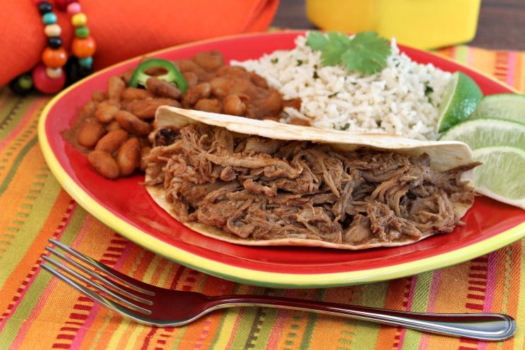 shredded pork soft tacos on a plate with beans and rice and lime wedges