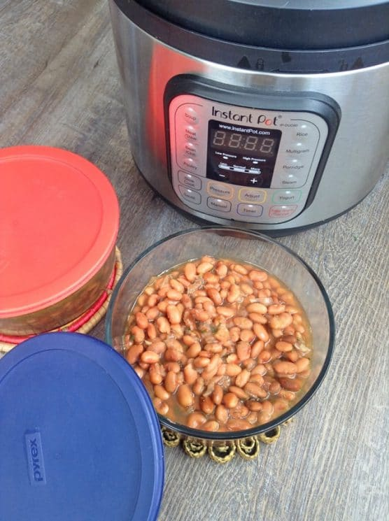 bowl of cooked beans in front of an instant pot
