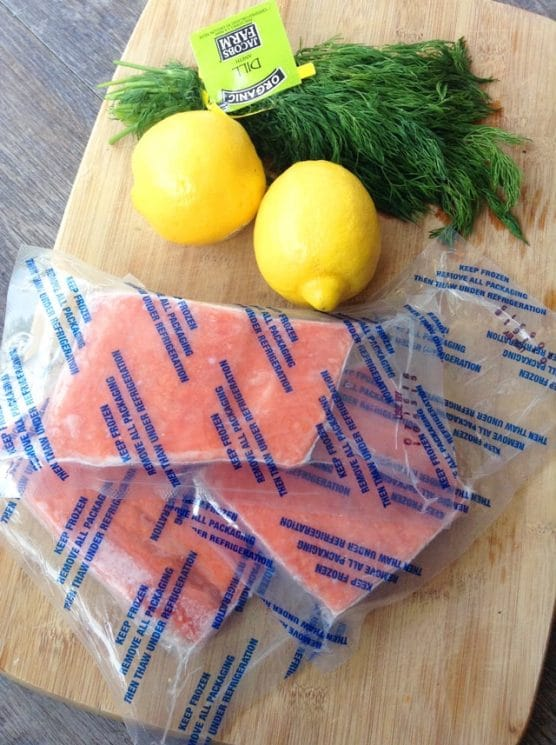 ingredients ready for prep: frozen salmon in bags, whole lemons, and a bunch of dill on a cutting board