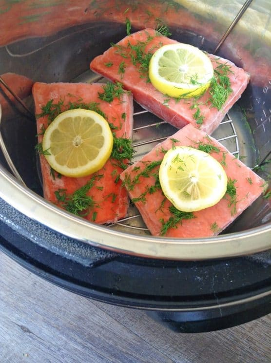 frozen salmon filets in the instant pot with fresh lemon slices and dill