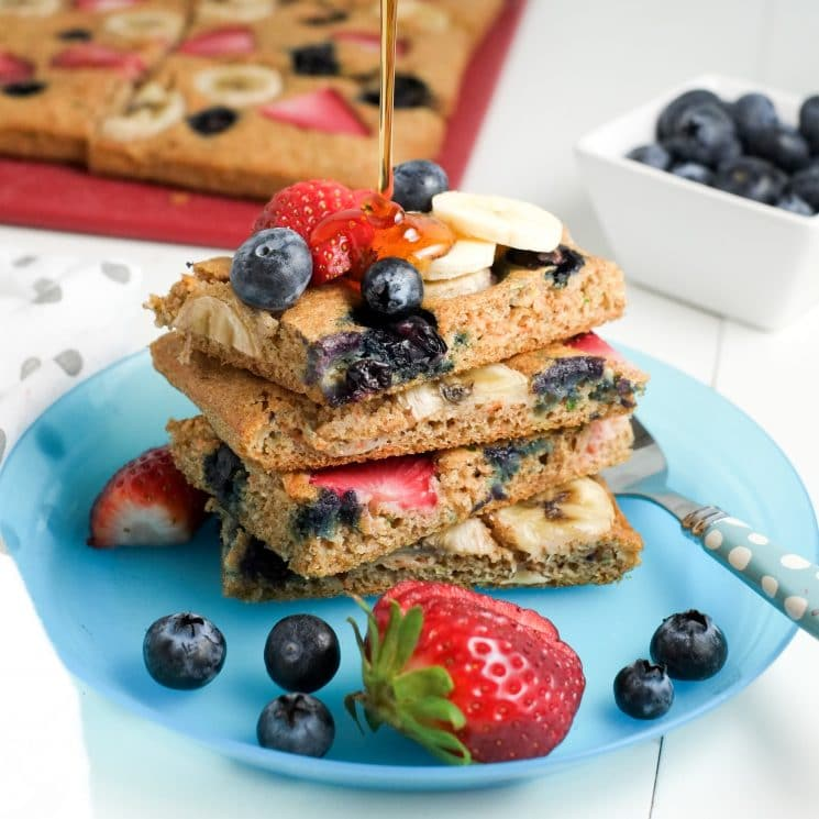 pancake squares topped with berries and bananas on a blue plate drizzled with syrup