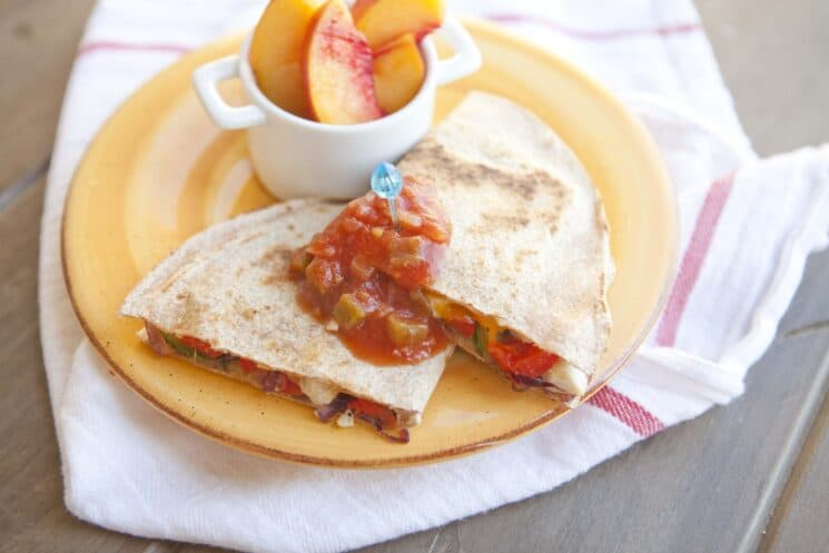 Grilled quesadillas with salsa and peaches on a yellow plate