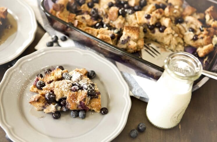 french toast casserole with blueberries with a serving placed on a white plate with a glass of milk