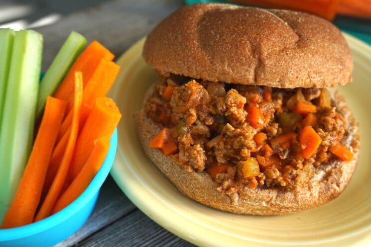 sloppy joes on a whole wheat bun served with carrot and celery sticks