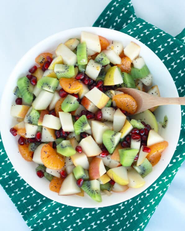 Fruit salad with apples, oranges, kiwi, pear and oranges in a white bowl with a green tea towel in the background