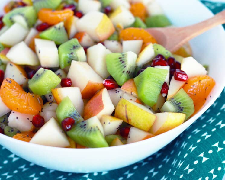 fruit salad made with apples, oranges, kiwi, pear and oranges in a white bowl with a green tea towel in the background