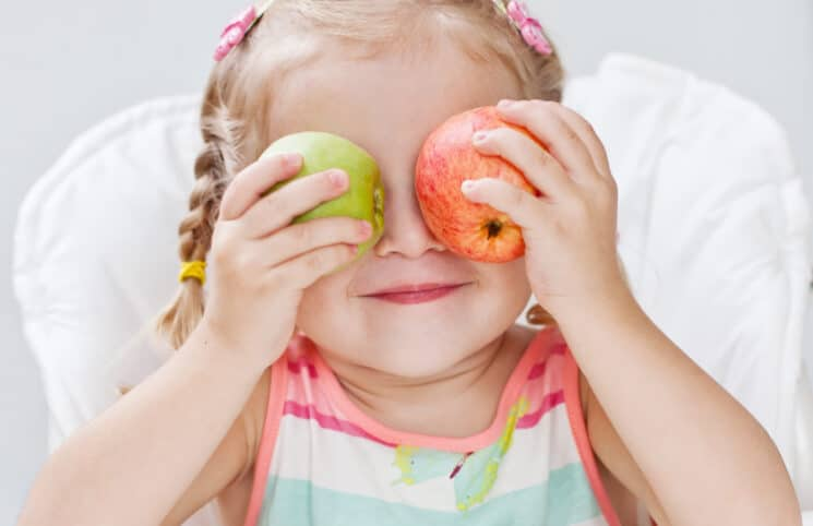 Healthy Snacks for Toddlers, toddler with apples over her eyes