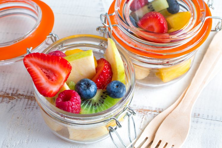 strawberries, raspberries, kiwi, blueberries in jars for a snack on the go