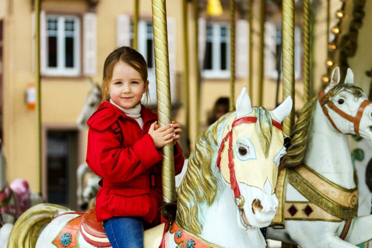 Little girl sitting on a carousel horse