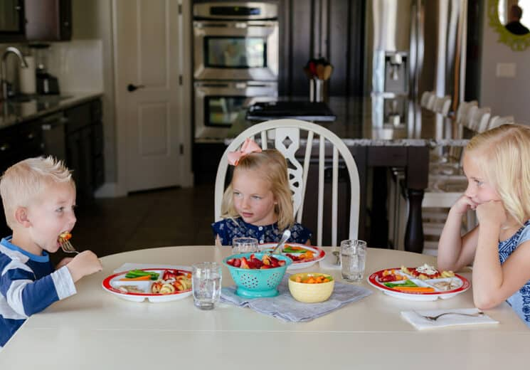 3 kids sitting at a dinner table eating and learning table manners